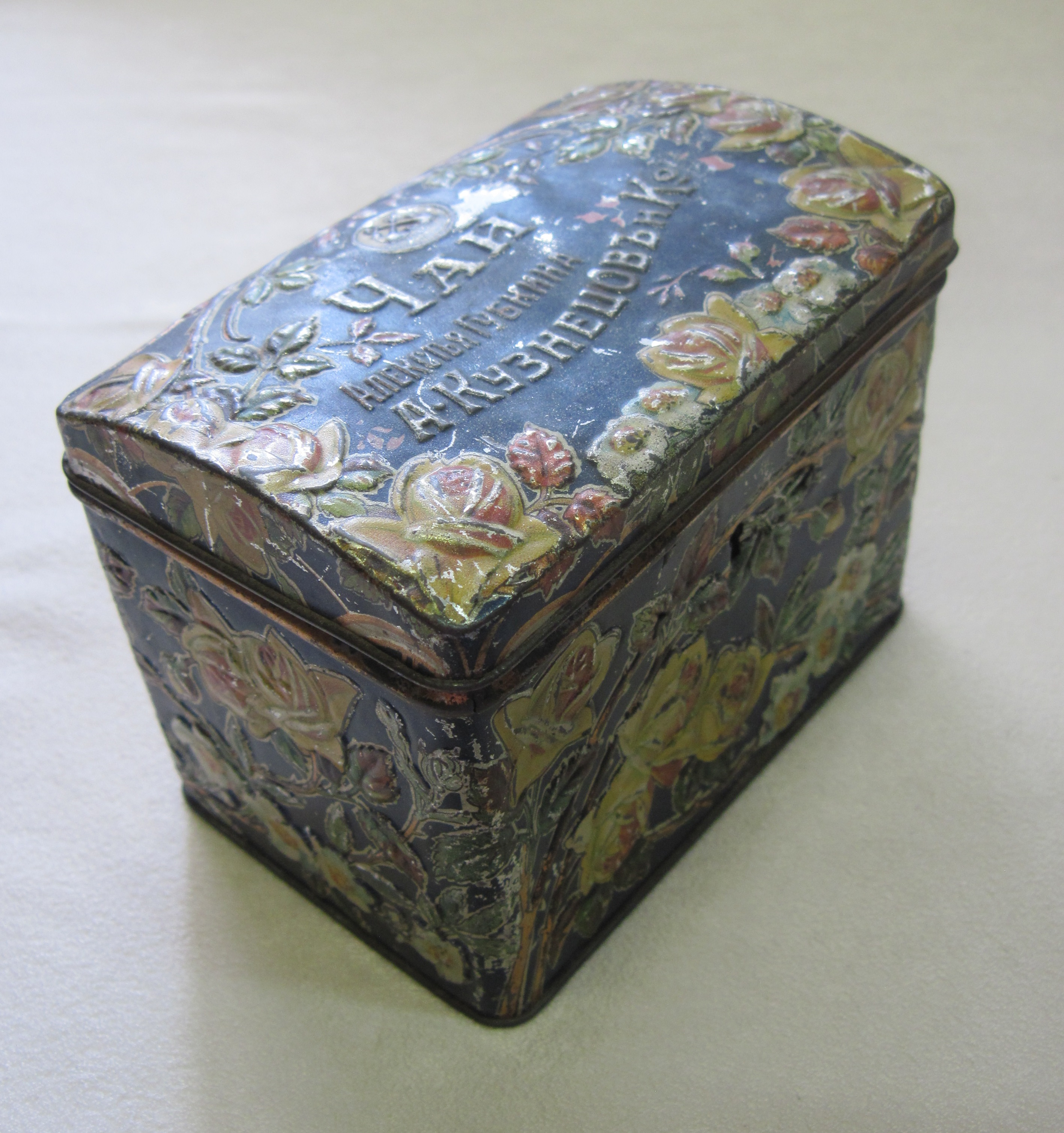 Коробка прямоугольная с двойной откидной крышкой. Общий фон синий. Рельефный цветочный узор на крышке и боковых стенках. На крышке торговый знак в виде двух якорей, надписи.